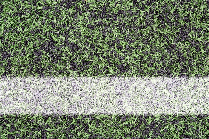 Detail of the cover of artificial sports turf with markings